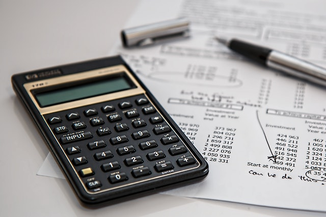 A black calculator next to coins and a notebook