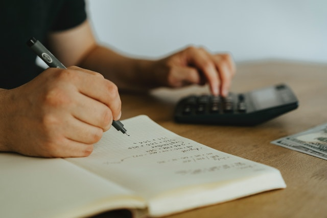 Close up of a person sitting at a desk, using a calculator with their left hand and holding a pen while writing in a notebook with their right hand.