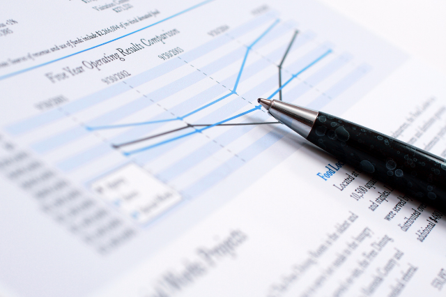 A pen lays on top of a financial report.
